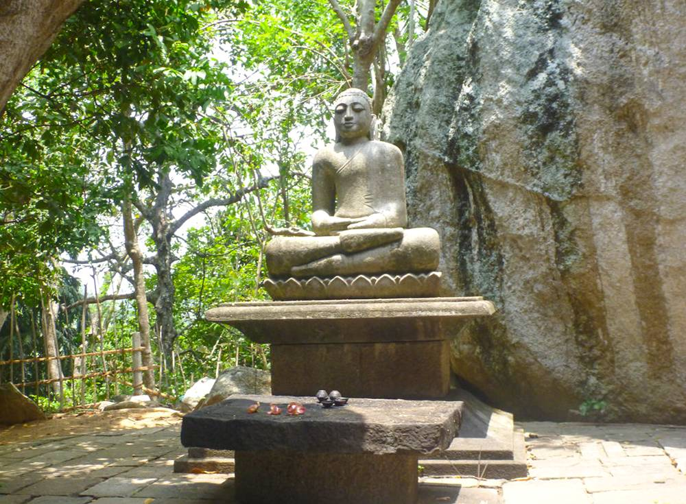 A Statue of Lord Buddha Near A Rock